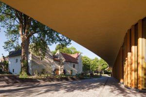 Door de gebogen dakvorm lijkt het paviljoen de oude hoeve te omarmen. Foto Mecanoo.