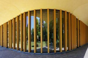 Ronde hoek met houten kolommen en gestucte luifel. Foto Jacqueline Knudsen