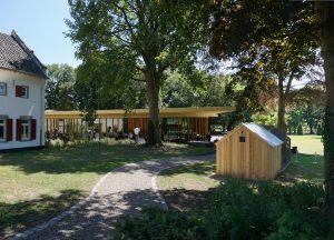 Vanaf de weg is een doorzicht gemaakt naar het landgoed met het nieuwe paviljoen. Zelfs het kippenhok (voorgrond rechts) is door Mecanoo ontworpen. Foto Jacqueline Knudsen