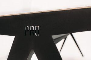 De naam van de bedenker staat duidelijk in het frame van de tafel.