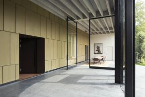 7.De tuinzaal heeft een 4,5 meter hoge taatsdeur. De halfronde glazen achterpui verbindt de foyer met de beeldentuin. Foto Christian van der Kooy