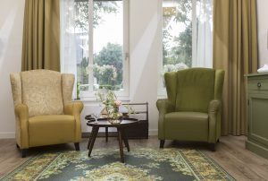 In de huiskamer is met retromeubilair een ouderwetse sfeer gecreëerd, waarin bewoners met dementie zich prettiger voelen. Om struikelen te voorkomen, is het tapijt op de vloer geprint