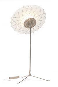 Filigree staande lamp met een ornamentachtige bloemenvorm projecteert een netwerk van schaduwen.