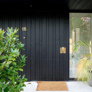 Entree met standaard huisnummer en handwerk deurknop.