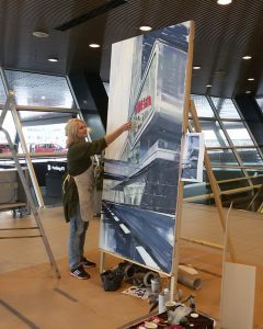 Pauline van Buringen aan het werk. 'In opdracht van designbureau dBOD maakte ik dit schilderij van het Elicium Centre.'