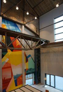 In de vide achter de hoofdentree hangt een oude kraan en zijn de oude spanten zichtbaar. Een muurschildering verwijst naar de historie van de plek.