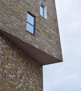 De gevelsteen van nieuwbouw is robuust maar contrasteert met de oude plaatwerkerij