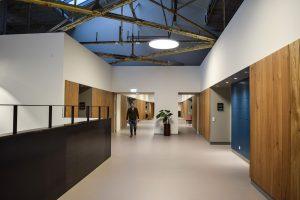 De brede middenstraat op de derde verdieping in Zware Plaatwerkerij. Stalen balustrades schermen de vides af.