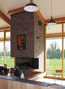 Bij voetbal- & cricketvereniging ASC in Oegstgeest zijn de houten draagconstructie en de opvallende gemetselde schoorsteen zowel van buiten als van binnen de grote blikvangers van het clubhuis. Ontwerp STOL Architecten, interieur Vormklub • Foto Jean-Paul Corèl.
