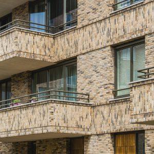 Horizontale banden van staand metselwerk lopen door in de gevlvlakken en balkons.