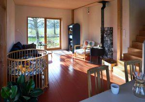 De woonkamer met houten vloer en leemstuc wanden. Foto Jacqueline Knudsen