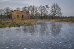 Het Oerhuis is omgeven door heide, velden en bossen, zicht vanuit oosten. Foto Jan Mateboer