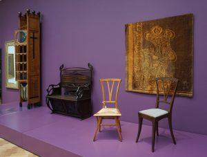 Arts & Crafts Den Haag: staande klok Wegerif , bankje en batik JohanThorn Prikker, en twee stoelen: links Henry vd Velde, rechts Thorn Prikker. Foto Jacqueline Knudsen
