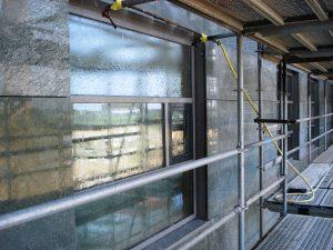Beproeving op waterdichtheid van een gevel met natuursteenplaten met open voegen. Het binnenblad wordt wel met water belast; door correct afplakken treden geen lekkages op