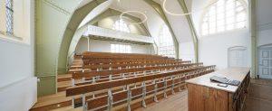 In de collegezaal is het aantal stoelenrijen gereduceerd. Foto Gerard van Beek.