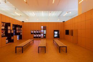 De entree van het Nederland paviljoen is een U-vormige muur van oranje lockers, met uitweidingen op het centrale thema Work, Body, Leisure. Vijf deuren bieden toegang tot vijf kamers