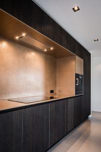 De nis in de keuken heeft een bronzen coating met een embossed effect. De koelkastdeur is greeploos in de kastenwand verborgen.