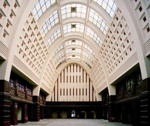 Centrale hal met hoog paraboolvormige gewelf van wit geverfd beton met een cassettenmotief en vensters in de top. Foto Omnan Investment Group