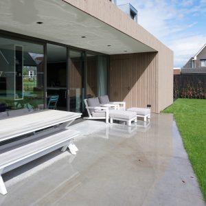 De gevlinderde betonvloer van het terras is superglad en na een regenbui spiegelt het zonlicht mooi tegen het plafond van het terras