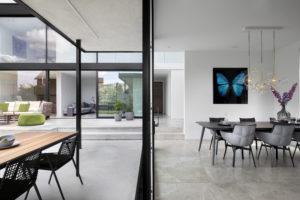 Visuele verbindingen tussen ruimtes binnen en buiten zijn belangrijk in dit huis.
