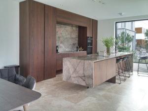 Het maatwerk meubilair in de keuken is bekleed met gepolijst marmer en notenhout. Een staalconstructie  ondersteunt het ogenschijnlijk  zwevende keukenblok
