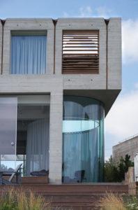 Op de 2e verdieping kraagt een volume uit met een patio. Onder de  uitkraging is een glazen erker geplaatst, uitgevoerd in gebogen glas. Foto Jacqueline Knudsen.