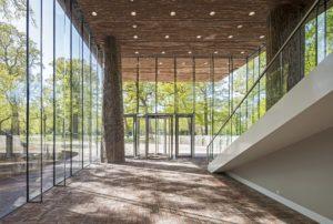 De entreehal van het LAM is volledig transparant. Hieruit rijzen vier met boomschors beklede kolommen omhoog, die het volume erboven dragen ● Foto Sjaak Henselmans