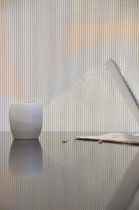 Merging wallpaper. Behangontwerp op basis van het onderzoek naar vervaging van kleuren. De textiele wandbekleding speelt een spannend spel met tijd en licht. Soms lichten delen op, soms ontstaat een kleurverloop door de veranderende lichtval