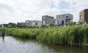 Aan de oever van Rieteiland-Oost staat de villa van V8 architects, 2e van rechts. De begane grond is in een duintalud verzonken . Foto Jacqueline Knudsen.