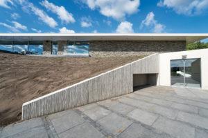 De volledig in beton uitgevoerde dragende benedenverdieping is grotendeels aan het zicht onttrokken door een op een terp lijkende verhoging. Hierdoor lijkt de bovenverdieping te zweven