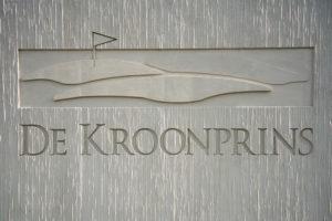 Door de verspringende reliëfdiepte wordt het in de betontextuur verwerkte logo van de golfbaan benadrukt