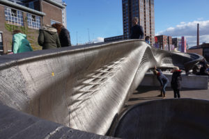 De 3D-geprinte MX3D brug van ontwerper Joris Laarman op het Ketelhuisplein op Strijp-S. Terwijl het publiek er overheen loopt, meten sensoren de bewegingen in de brug, die later dit jaar op de Amsterdamse Wallen wordt geplaatst • Foto Jacqueline Knudsen