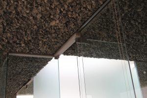 Het plafond bestaat uit scherpe brokken glasschuim, die geluidsabsorberend werken. Het gaat met zijn ruwheid een esthetische wisselwerking aan met de strakke transparante glaswanden. Koven voor binnenwanden zijn bij het storten van het dak direct al meegenomen