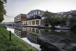 Zicht langs de Vaartsche Rijn richting binnenstad, met links naast Keramus wooncomplex de Trip en in de verte het nieuwe station. Foto Walter Frisart / FOTOWERK