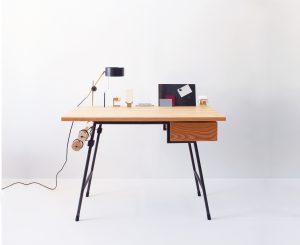 Back-to-Basic desk heeft een essenhouten blad op een blauw stalen frame. De geïntegreerde maar wel individueel verplaatsbare lamp, koperen accessoires en een magnetisch paperclipbakje vormen samen een stad