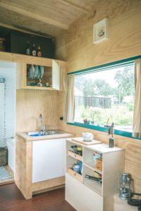 Om de leefruimte zo goed mogelijk te benutten staat de keuken overdwars met een inklapbaar tussenblad voor de badkamerdeur • Foto Peter Hermeling / Blue Monque