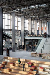 Als coulissen staan in de zijbeuken van de LocHal Tilburg vakwerkkolommen met platen blauwstaal, die de nieuwe vloeren dragen en als leidingschacht dienen.