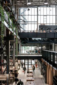 Binnenstraat met links werkplekken aan de kolommen in het midden de hoofdentree, op 1e verdieping Seats2Meet en op 2e studieplekken