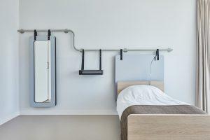 Aan een doorlopende buis kunnen objecten aan leren riemen hangen, als een spiegel, een headbord of een kastje. Foto Jeroen van der Wielen