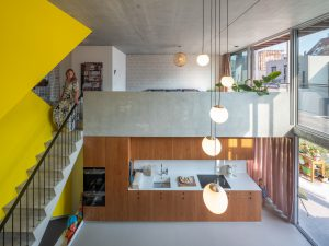In een centraal trappenhuis lopen de trappen van beide woningen. De trap naar de bovenwoning heeft een gele omkleding.