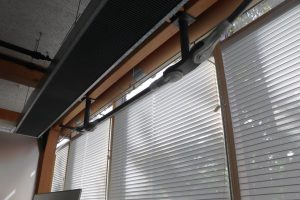 Kartonnen ventilatiekanalen en de houtconstructie langs de gevel