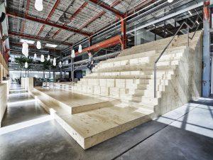 Centraal in het nieuwe kantoor van Designbureau VanBerlo is een hoog atrium met daaromheen alle werkruimtes. Een grote houten trap doet dienst als tribune. Foto Tycho Merijn i.o.v. Atelier Van Berlo