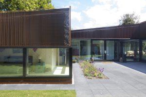 De entree ligt aan het binnenterrein en komt centraal in de woning uit op een hoge lichte ruimte