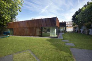Het dak is uitgevoerd als een groen dak en loopt vanaf de woonkamer naar rand af onder een flauwe helling. Op termijn raakt de cortenstalen gevel begroeid met groene klimplanten