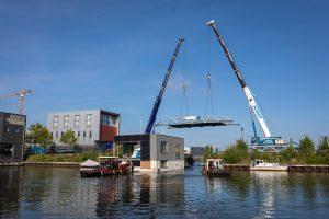 Mei 2019: om de arken naar hun plaats te slepen most een hoogwerker de brug optillen. Hier gaat de ark van Marjolein Smeele onder de brug door. De zuidgevel is geheel met zonnepanelen bekleed.