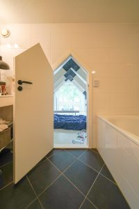 Een kleine deur geeft vanuit de badkamer toegang tot het hogere gedeelte van de klimkamer