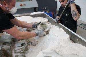 Bij Sandhelden wordt een object laag voor laag opgebouwd in 98% zand en 2% hars als binder, die het zachte witte zand donkergrijs tint. Hier de productie van de Dervish