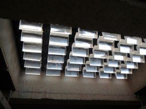 De nieuwe prismatische glasblokken sturen het licht in de onderliggende ruimte een kant op. Inzet: bovenzijde van de glasvloer