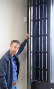 Architect Bart Cilisssen toont de te openen delen in de gevel, die zich achter de open houten gevelbeleding bevinden
