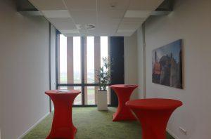 De kantoren an de westzijde grenzen aan een gevel met een groot dakoverstek en verticale wrc lamellen